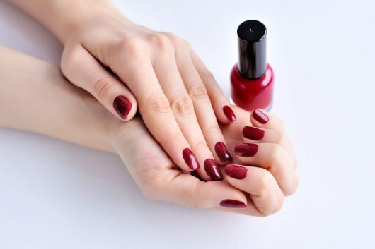 hands-of-a-woman-with-dark-red-manicure-and-nail-P5VNS4S.jpg